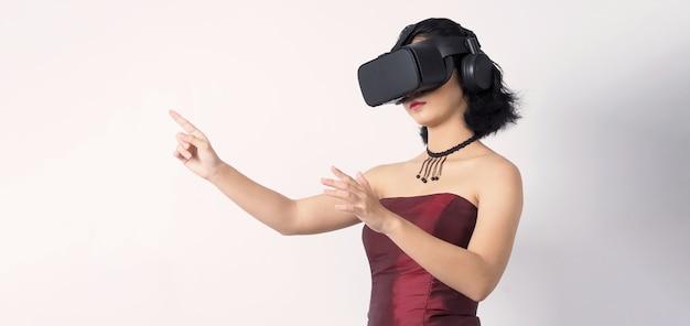 Donna adolescente asiatica che indossa la cuffia vr o di realtà virtuale per entrare nel mondo della simulazione digitale per imparare, viaggiare o giocare e altro ancora.