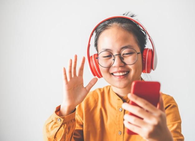 Adolescente asiatico in abito giallo che parla su smartphone per videochiamate facetime durante l'epidemia di coronavirus covid-19, distanza sociale, lavoro da casa nuovo concetto normale