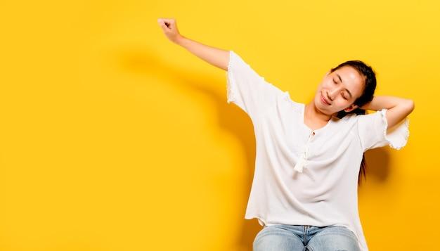 Adolescente asiatico che si sente felice. sorridendo e guardando la telecamera per scattare foto di se stesso fotografia in studio giallo concetto di sorriso, varie presentazioni, spazio libero