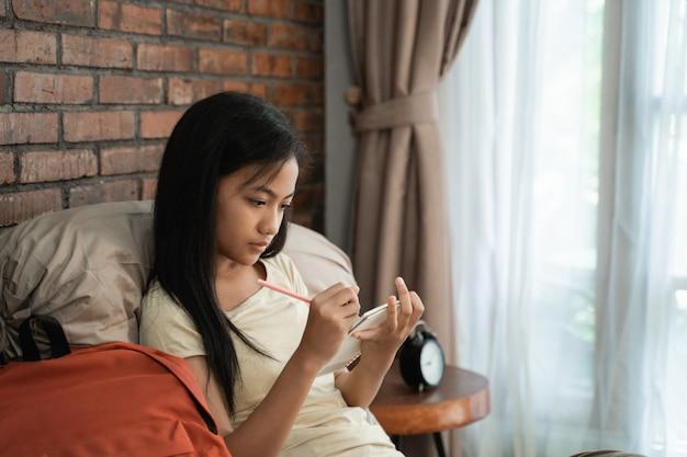 Adolescente asiatico che studia a casa