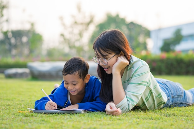 Adolescente asiatica insegna il ragazzo con amore e divertimento nei prati verdi