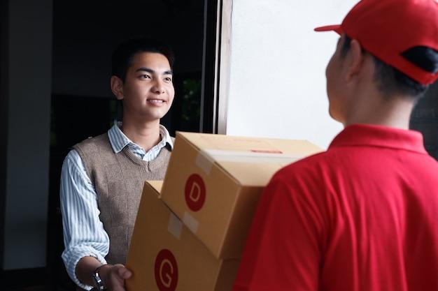 L'adolescente asiatico accetta rifornimenti alla porta, dopo che l'epidemia di covid-19 ha messo fine alle persone che fanno ancora acquisti online.