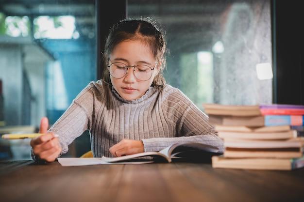 Adolescente asiatico che fa il lavoro domestico della scuola nella stanza della biblioteca