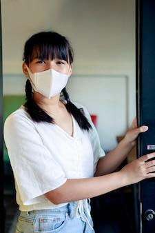 Adolescente asiatico che indossa la maschera di protezione per il viso in piedi alla porta aperta