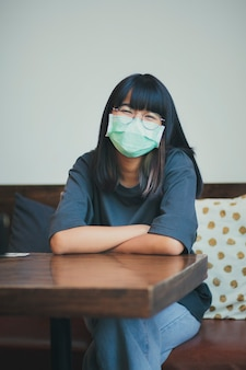 Adolescente asiatico che indossa la maschera per il viso di protezione seduto nel soggiorno di casa