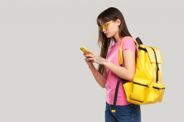 Una donna adolescente asiatica con gli occhiali a forma di cuore tiene in mano un telefono cellulare. nuova pubblicità di gadget