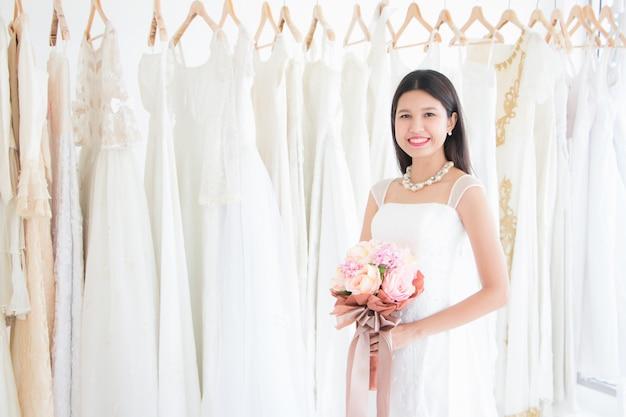 Una sposa thailandese asiatica indossava un abito da sposa bianco e aveva in mano un mazzo di fiori. sorrideva felice mentre provava il vestito nella stanza in affitto e lo tagliava.