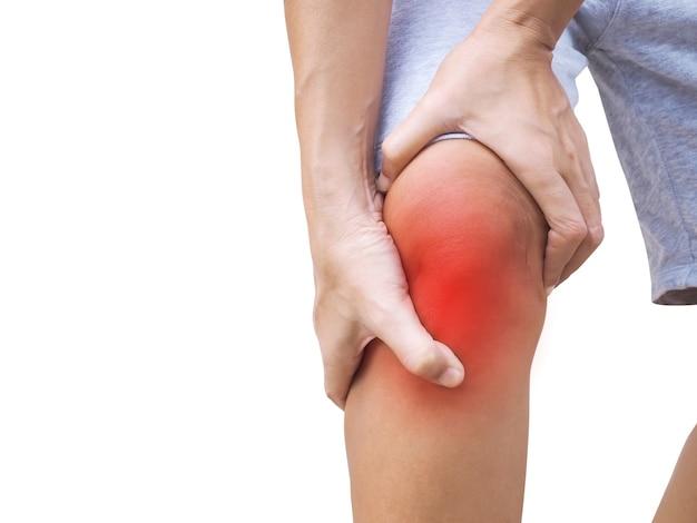 Donna tailandese asiatica che soffre di dolore al ginocchio e dolore alle gambe, usando le mani per massaggiare il corpo isolato su sfondo bianco.