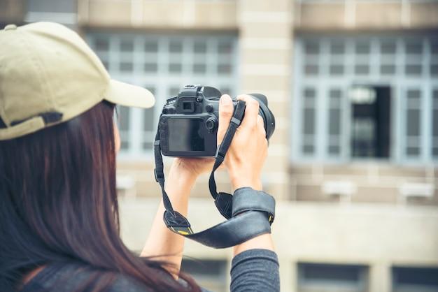 Turista asiatico utilizzando una telecamera professionale. donna giovane viaggiatore con zaino e macchina fotografica nella città vecchia.
