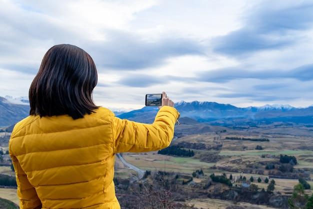 Donna turistica asiatica che cattura foto con il telefono cellulare nell'isola del sud di queenstown in nuova zelanda