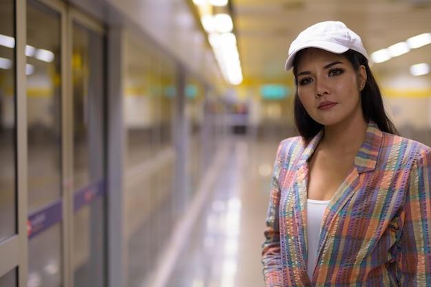 Donna turistica asiatica in attesa del treno nella stazione della metropolitana