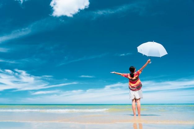 Donna turistica asiatica con unbrella bianco che si rilassa sulla spiaggia di giorno, concetto di viaggio di vacanze estive