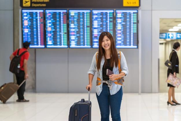 Viaggiatore asiatico con i bagagli con il passaporto che cammina sopra il bordo di volo