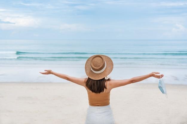 La donna asiatica del viaggiatore decolla la mascherina medica alla spiaggia. nuovo concetto normale, di viaggio e di vacanza