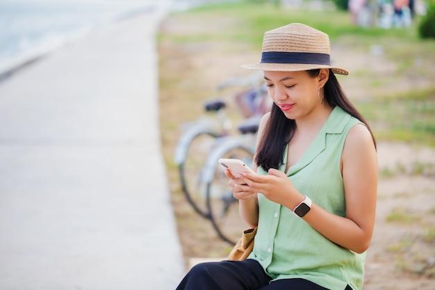 Donna asiatica del viaggiatore che viaggia con la bicicletta e utilizza lo smartphone in spiaggia in riva al mare