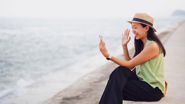 Donna asiatica del viaggiatore che utilizza la videochiamata dello smartphone online in spiaggia in riva al mare