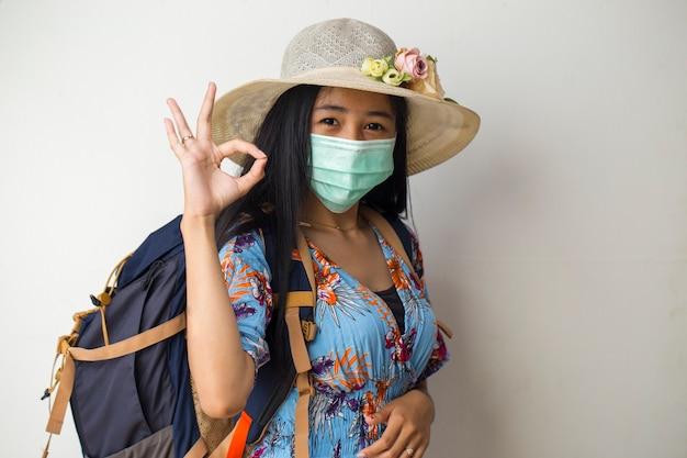 Donna asiatica del viaggiatore che indossa la maschera protettiva che mostra segno giusto con le dita isolate su priorità bassa bianca