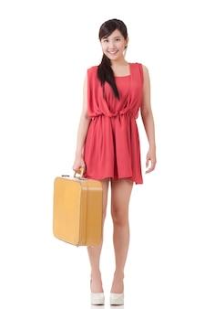 Donna asiatica in viaggio con valigia, ritratto a figura intera con la riflessione su sfondo bianco studio.