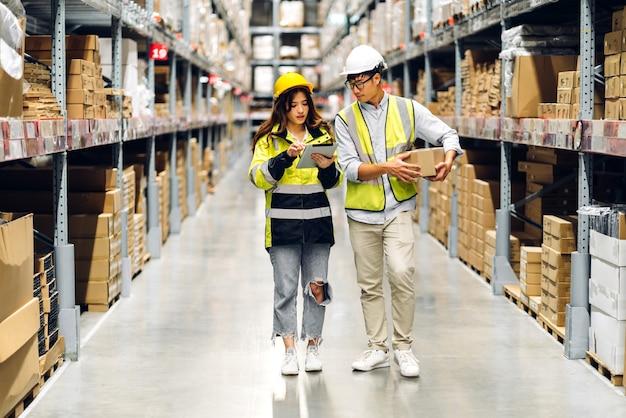 Assistente tecnico asiatico due nei dettagli di ordine della squadra dei caschi sul computer tablet per il controllo di merci e forniture