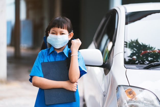 Lo studente asiatico uniforme indossa una maschera per proteggere il virus corona o covid-19