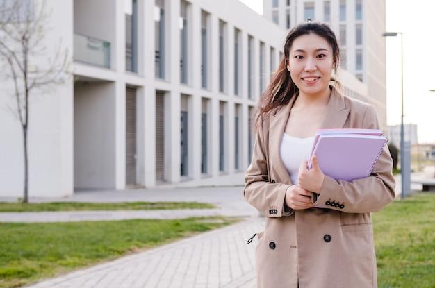 Studente universitario asiatico che tiene le cartelle mentre si trovava all'aperto presso il campus universitario