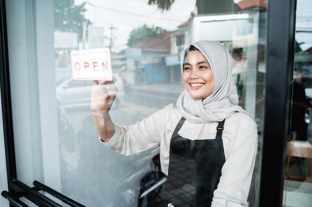 Il cameriere velato asiatico tiene un cartello aperto