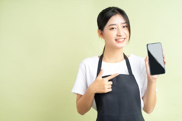 Cameriera asiatica che tiene il suo telefono con una faccia allegra