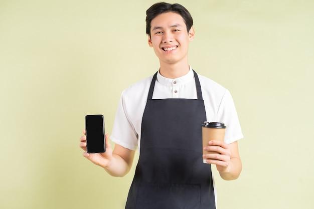 La cameriera asiatica che tiene un telefono e un bicchiere di carta in una mano sta sorridendo