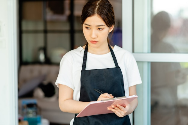 La cameriera asiatica sta controllando la camera d'albergo dopo il check-out degli ospiti