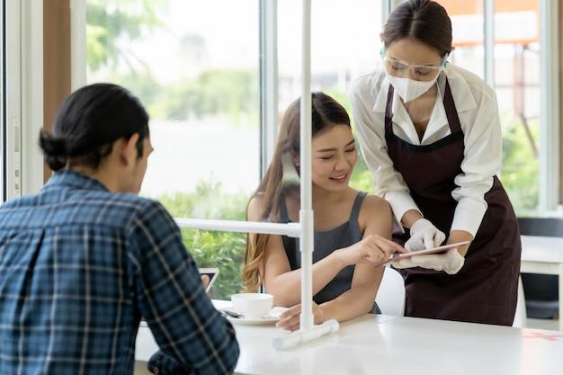 Menu di scarpe asiatiche cameriera con tablet.