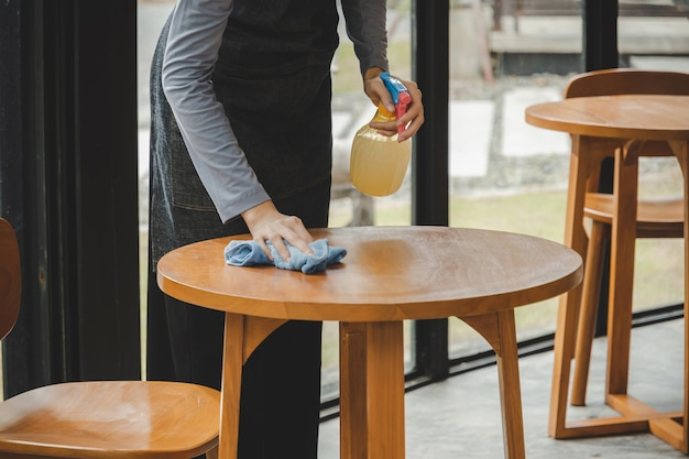 Donna asiatica di servizio del personale della cameriera nel tavolo di pulizia del grembiule con spray disinfettante per proteggere l'infezione da coronavirus (covid-19) nell'hotel del ristorante della caffetteria. nuovo concetto normale