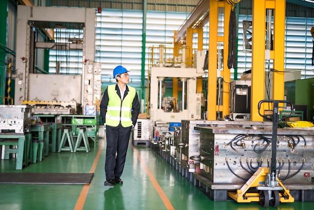 Il responsabile del magazzino asiatico con l'elmetto protettivo cammina per guardare le macchine nella fabbrica di produzione