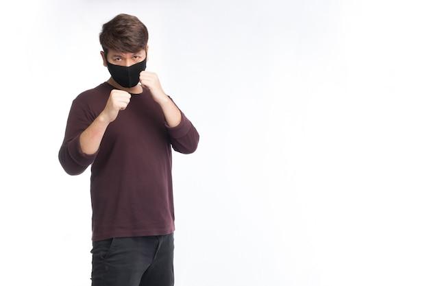 L'asiatico indossa una maschera chirurgica nera, posa la guardia di boxe