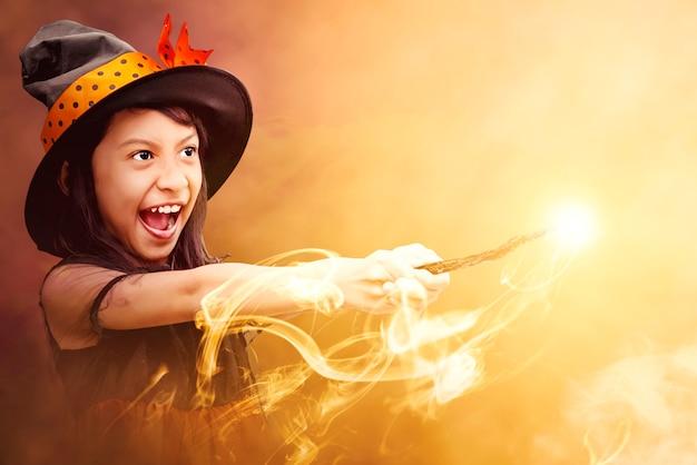 Strega asiatica bambina che usa la bacchetta magica con un fuoco mistico su uno sfondo drammatico
