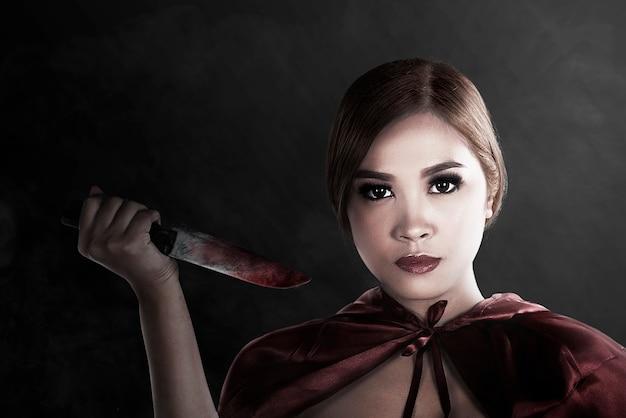 Strega asiatica che tiene in mano un coltello insanguinato in piedi con un muro nero sullo sfondo