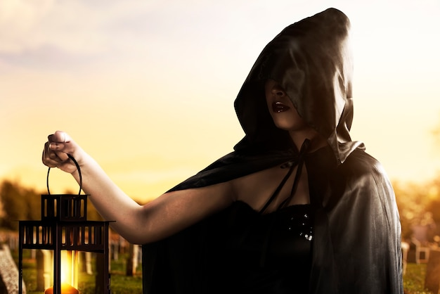Strega asiatica con un mantello nero che tiene una lanterna in piedi sul cimitero