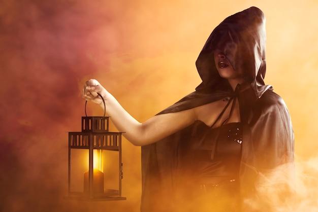 Strega asiatica con un mantello nero che tiene una lanterna in piedi con uno sfondo drammatico