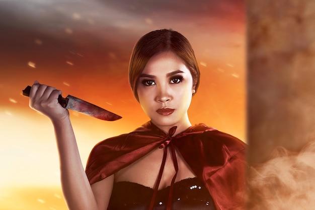 Strega asiatica con un mantello che tiene un coltello in piedi con uno sfondo drammatico