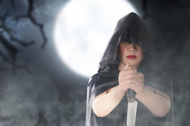 Strega asiatica con un mantello che tiene un coltello in piedi con lo sfondo della scena notturna