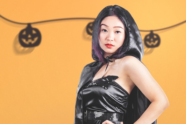 Strega asiatica con un mantello in piedi con uno sfondo colorato