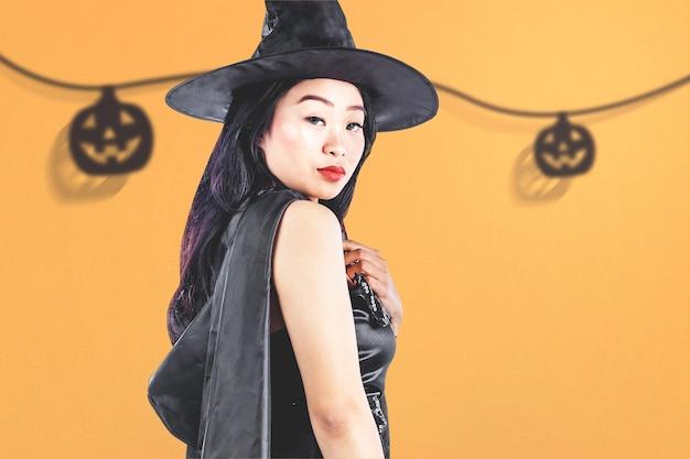 Strega asiatica con un cappello in piedi con uno sfondo colorato