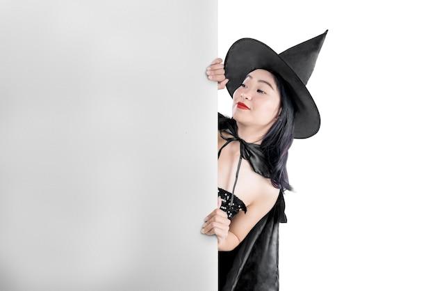 Donna asiatica della strega con il cappello che sta con la lavagna vuota isolata