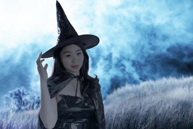 Strega asiatica con un cappello in piedi con lo sfondo della scena notturna