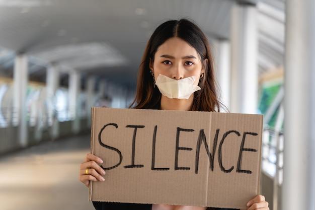 Attiviste asiatiche con striscioni che protestano per la democrazia e l'uguaglianza. uomini e donne fanno una protesta silenziosa per la democrazia e l'uguaglianza