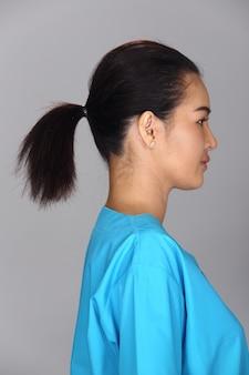 La donna asiatica dopo l'applicazione compone la camicia blu di stile dei capelli neri. nessun ritocco, viso fresco con acne, pelle bella e liscia. sfondo grigio con illuminazione da studio, vista posteriore sul retro