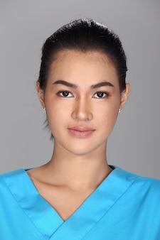 La donna asiatica dopo l'applicazione compone la camicia blu di stile dei capelli neri. nessun ritocco, viso fresco con acne, pelle bella e liscia. sfondo grigio di illuminazione dello studio