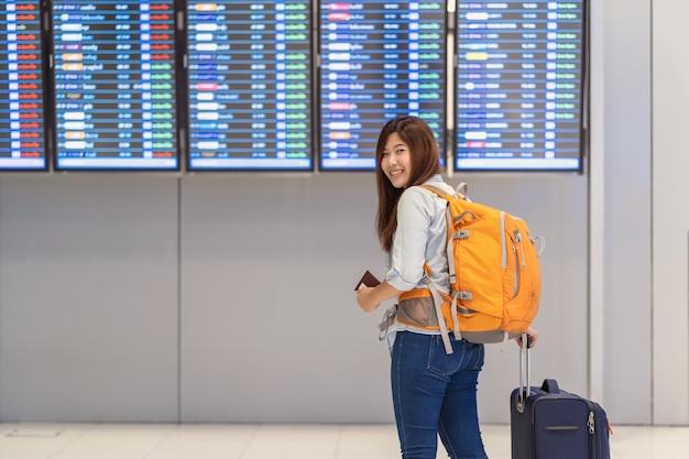 Viaggiatore con zaino e sacco a pelo asiatico della donna o viaggiatore con bagagli con il passaporto che cammina sopra il verro di volo