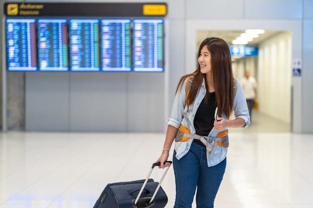 Viaggiatore con zaino e sacco a pelo asiatico della donna o viaggiatore con bagagli con camminare del passaporto