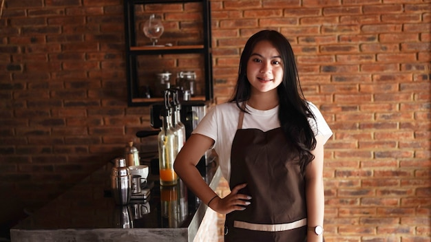 Macchina fotografica di sguardo smilling del barista della donna asiatica al caffè