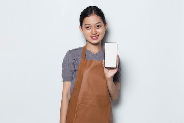Donna asiatica barista indossare grembiule dimostrando cellulare servizio cafe concept